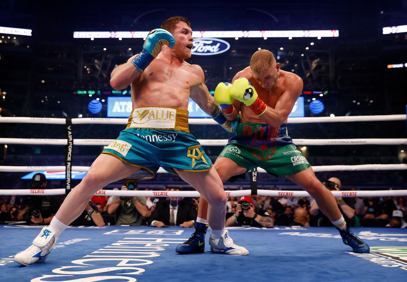 Boxer Canelo Alvarez (left) lands a punch on Billy Joe Saunders during their super middleweight title fight at AT&T Stadium in Arlington, Saturday, May 8, 2021. Saunders couldn't go on in the ninth round because he sustained an eye injury and could not see. (Tom Fox/The Dallas Morning News)