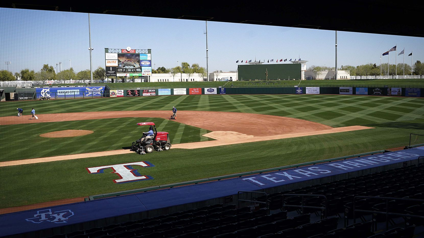 Groundskeepers work on the field at Surprise Stadium in preparation for the Texas Rangers Cactus League opening game against the Kansas City Royals on Saturday, Feb. 27, 2021, in Surprise, Ariz.