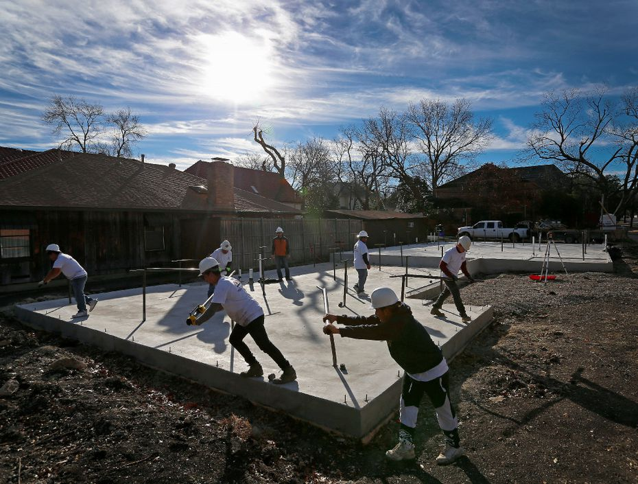 Workers push bars to raise the concrete slab at a home construction site in University Park. The technique that the Tella Firma system uses helps protect the foundation from damaging active soil movement.