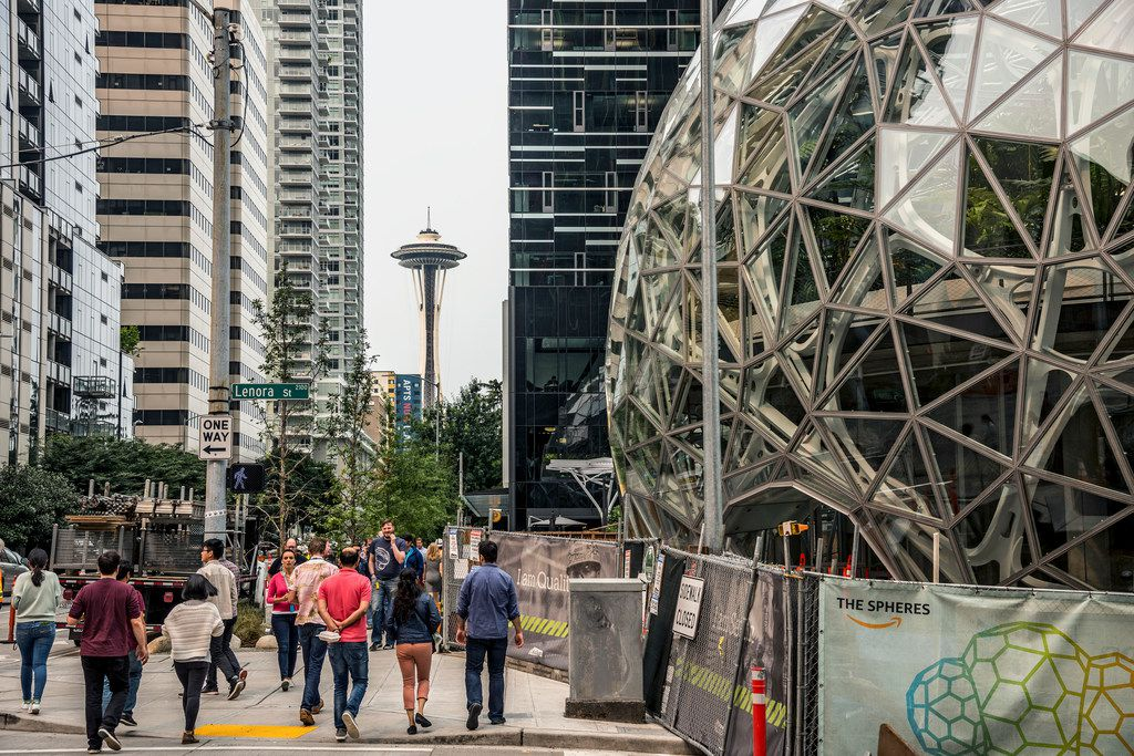 With the Space Needle observation tower visible in the distance, pedestrians walk past a recently built trio of geodesic domes that are part of the Seattle headquarters for Amazon on Sept. 7, 2017. The online retail giant said it was searching for a second headquarters in North America in 2017, a huge new development that would cost as much as $5 billion to build and run, and house as many as 50,000 employees.