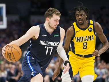 Dallas Mavericks guard Luka Doncic (77) takes the ball down court with Indiana Pacers forward Justin Holiday (8) during the third quarter of an NBA game between the Indiana Pacers and the Dallas Mavericks on Sunday, March 8, 2020 at American Airlines Center in Dallas.