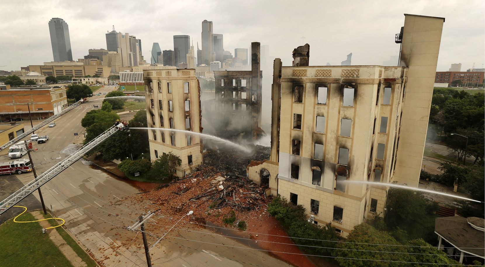 Dallas firefighters poured water on the historic Ambassador hotel just south of downtown Dallas.
