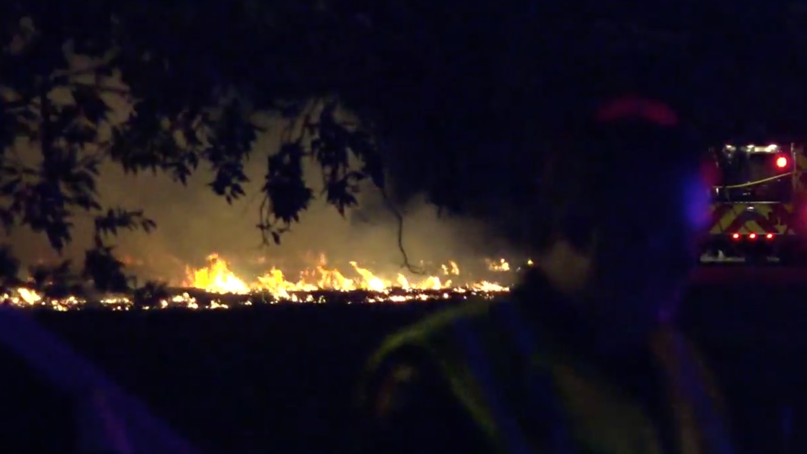 Fire crews in Plano work to put out a grass fire sparked during the city's fireworks display for the Fourth of July 2020.