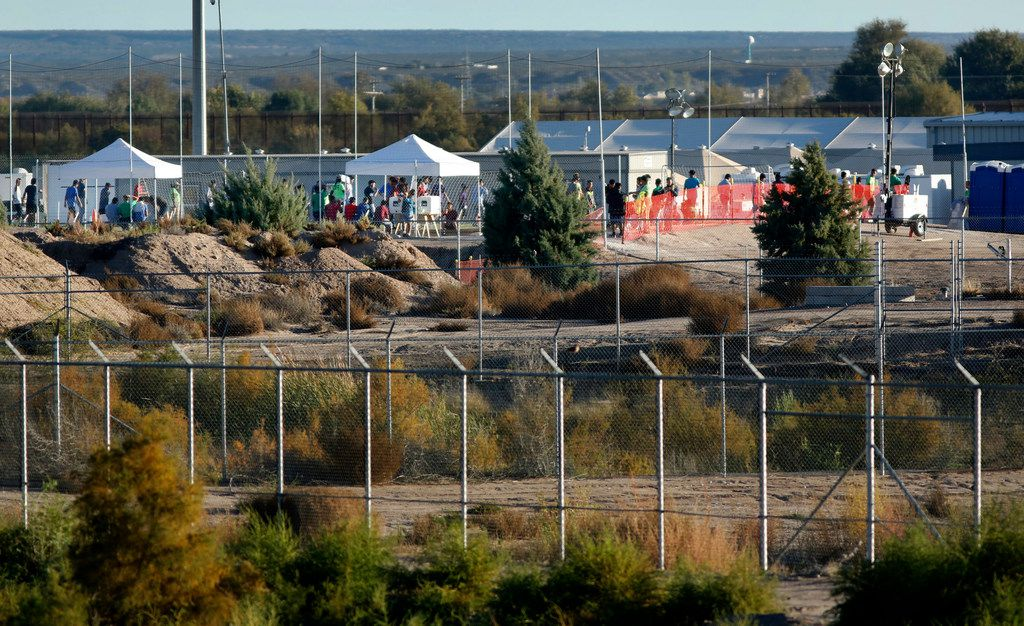 Behind layers of fences, migrant kids play soccer at the tent city on November 8, 2018.