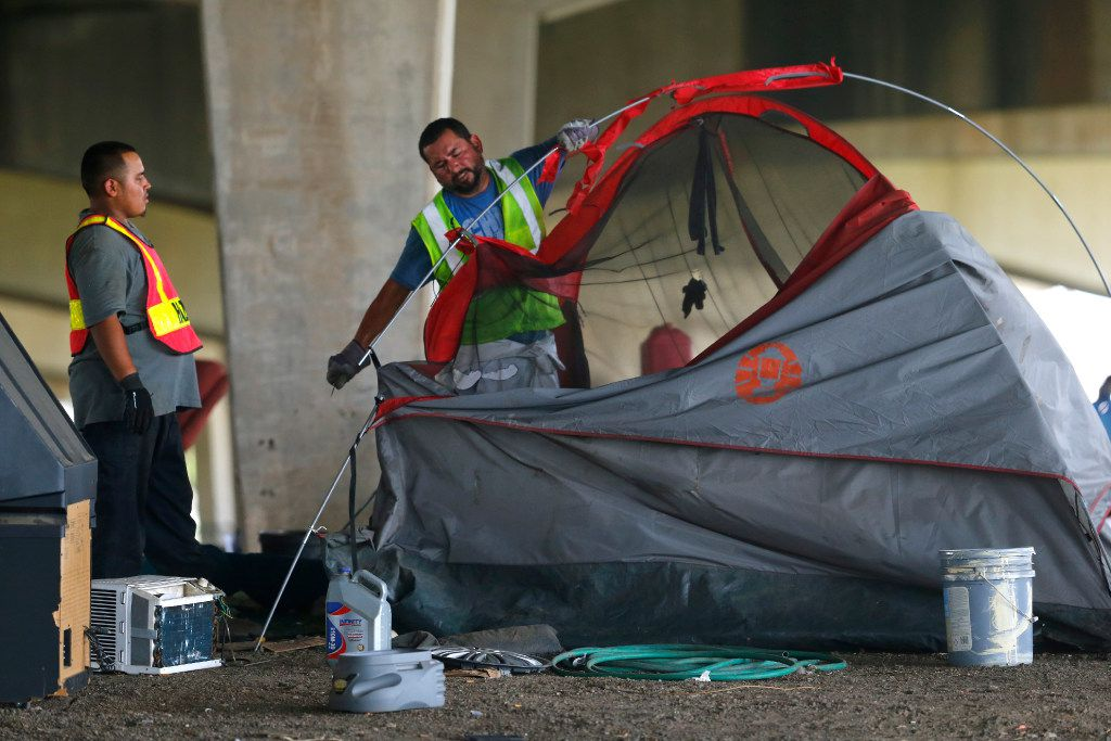 Hazardous material workers rip up a tent after the city closed a large homeless encampment under Interstate 30 on 3rd Avenue in Dallas on July 25, 2017.