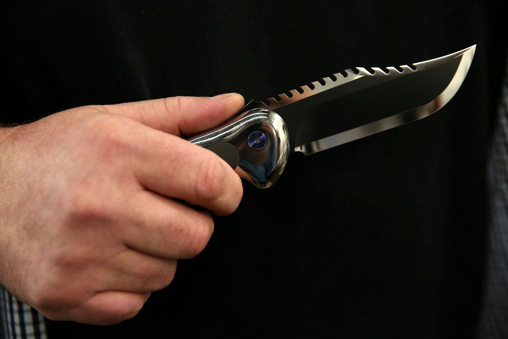 Todd Begg holds the Baker Team knife, modeled after the Rambo knife, he crafted at his shop in Dallas.