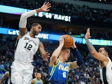 Dallas Mavericks forward Kristaps Porzingis (6) pulls down a rebound between San Antonio Spurs center LaMarcus Aldridge (12) and forward Trey Lyles (41) during the second half of an NBA basketball game at American Airlines Center on Thursday, Dec. 26, 2019, in Dallas.