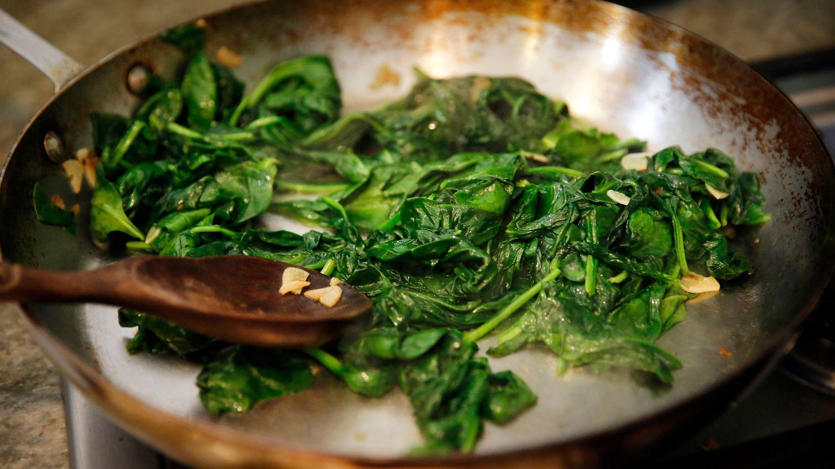 Julian Barsotti sautes spinach with garlic, to be layered into his 21-layer timpano.