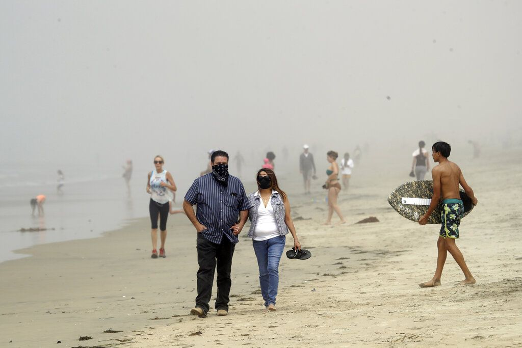 People wear masks as they walk on the beach Sunday, April 26, 2020, in Huntington Beach, Calif. A lingering heat wave lured people to California beaches, rivers and trails again Sunday, prompting warnings from officials that defiance of stay-at-home orders could reverse progress and bring the coronavirus surging back. (AP Photo/Marcio Jose Sanchez)
