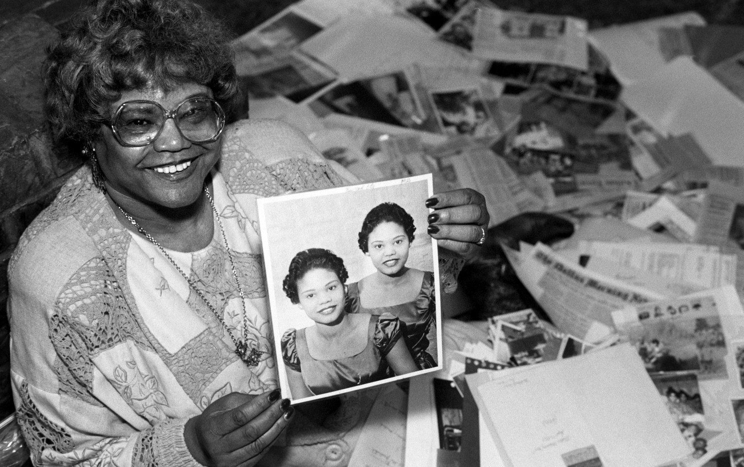 In this 1994 photo, Ina Bell Daniels McGee holds a picture from 1956 of her and her twin sister, Nina. Surrounding her is a trunk full of memorabilia from their life together.