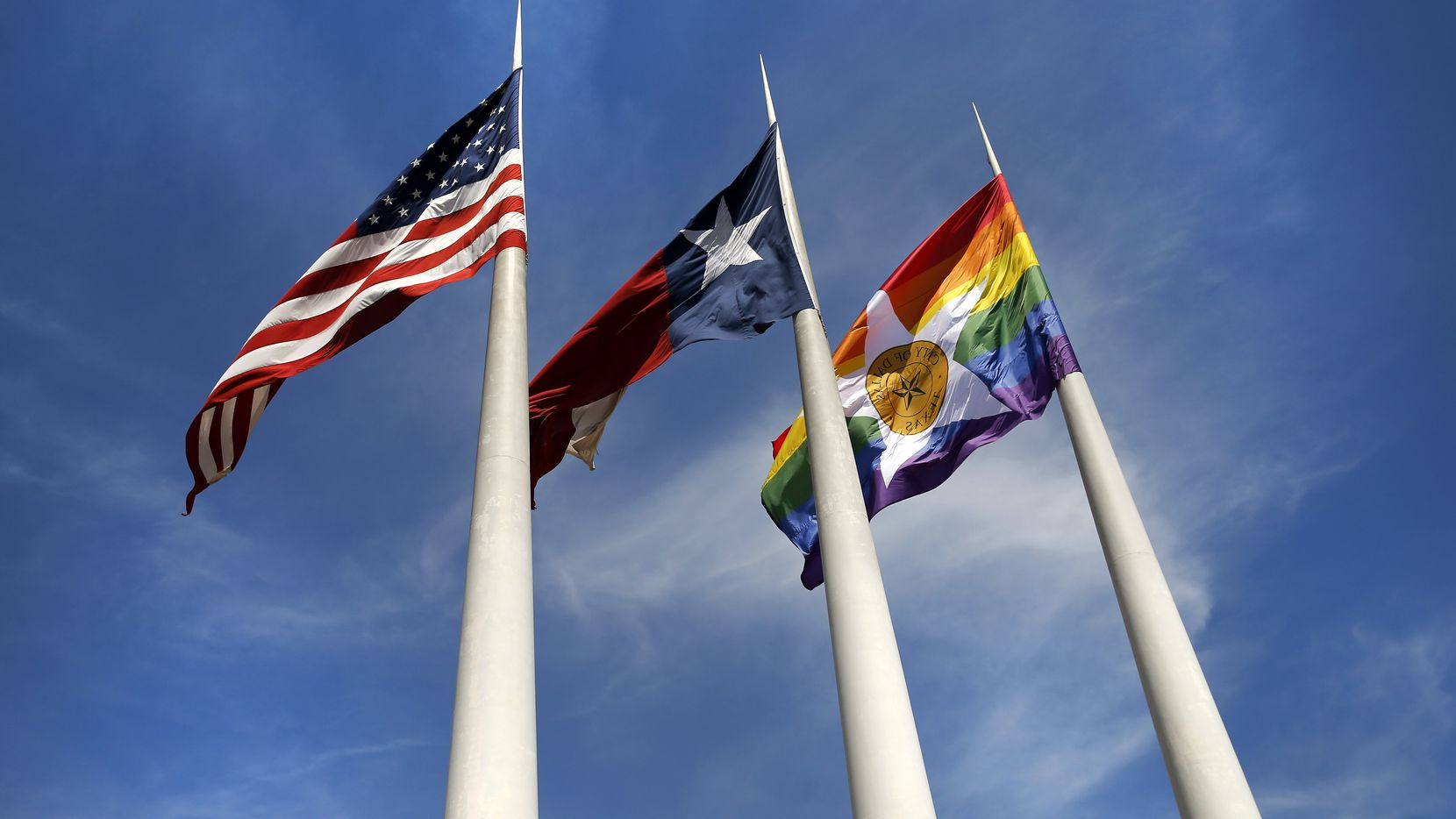 In honor of Pride Month, the City of Dallas' Pride flag (right) flies alongside the Texas and U.S. flags outside of City Hall in downtown Dallas, June 18, 2020. Dallas City Council passed a resolution directing the city manager to fly the flag the rest of the month. The flag will also fly for the month of June going forward. (Tom Fox/The Dallas Morning News)