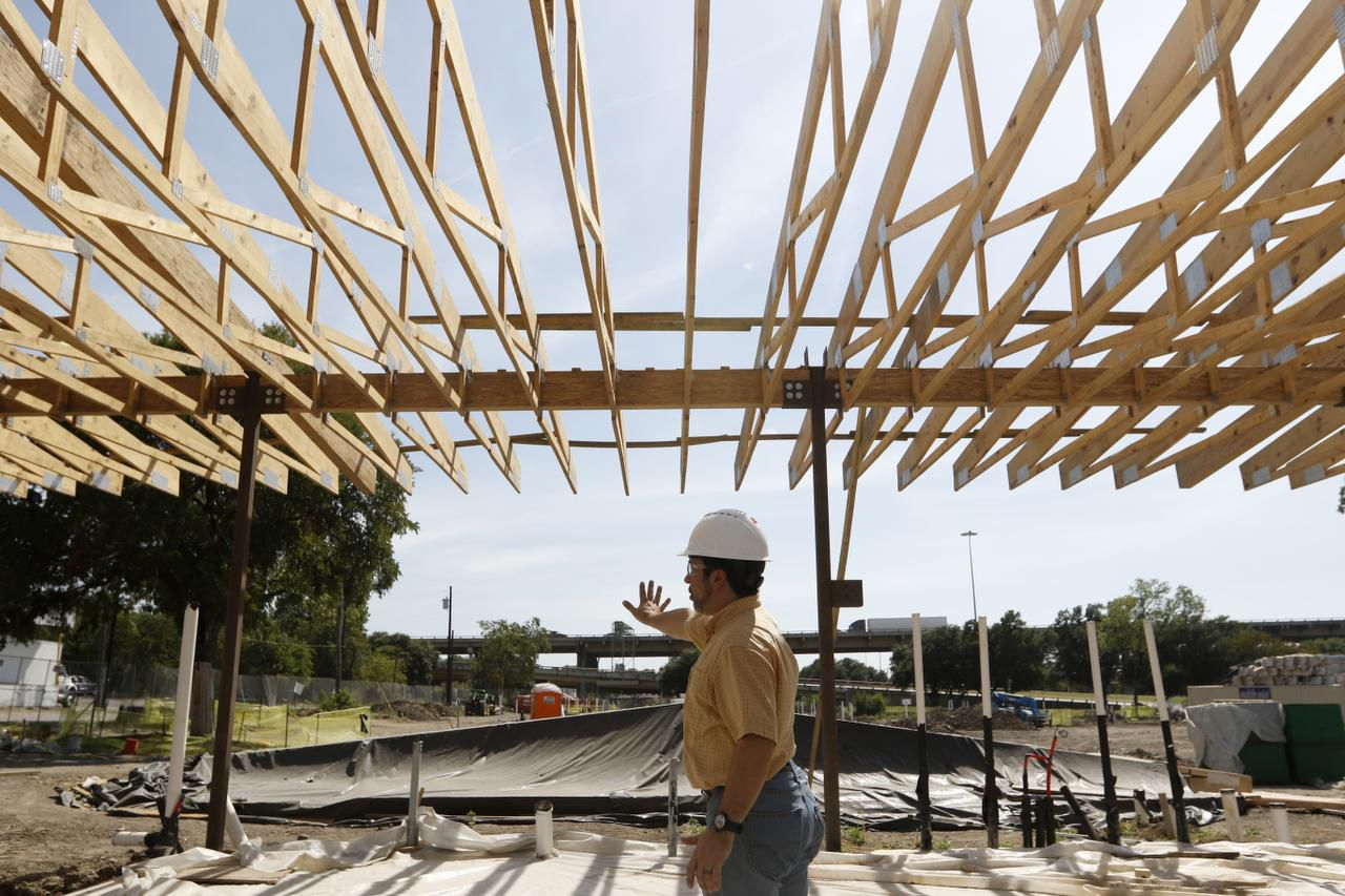 """Keith Ackerman, executive director of The Cottages at Hickory Crossing, leads a construction tour of the project, which is designed to provide housing for the chronically homeless and help each resident """"hopefully be a contributor to society once again."""""""