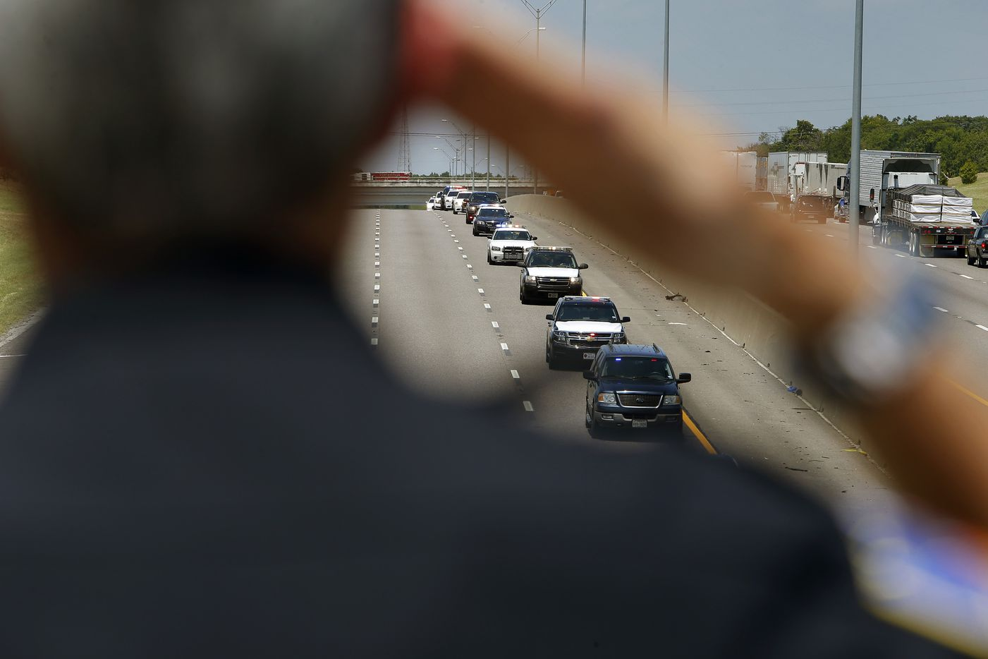 Duncanville police officers salute the funeral procession for DART Officer Brent Thompson on Interstate 20 in Duncanville, Texas on Wednesday, July 13, 2016. Thompson and four other officers were killed during an attack during a peaceful Black Lives Matter protest on July 7, 2016.