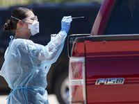 A trabajadora de la salud hace una prueba de covid-19 a un paciente en Los Barrios Unidos Clinic. Para los que quieren resultados más rápidos un restaurante ofrece las preubas por $200.