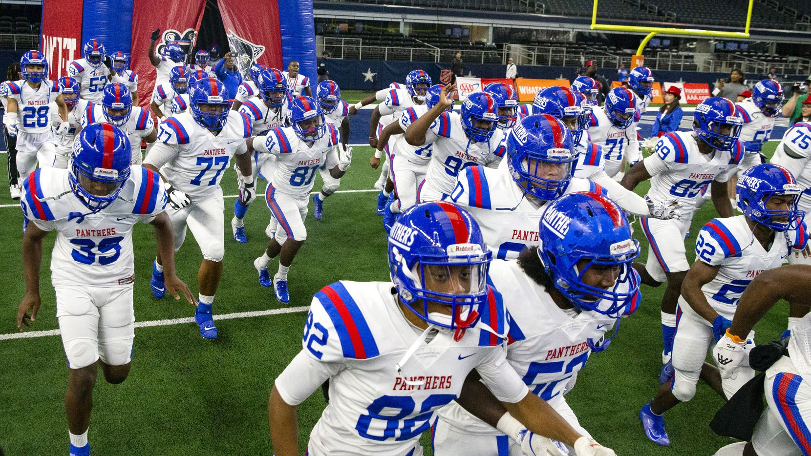 The Duncanville varsity football team emerges from an inflatable arch at the beginning of the Class 6A Division I area-round high school football playoff game against Flower Mound high school at the AT&T Stadium in Arlington, Texas, on Saturday, November 23, 2019. (Lynda M. Gonzalez/The Dallas Morning News)