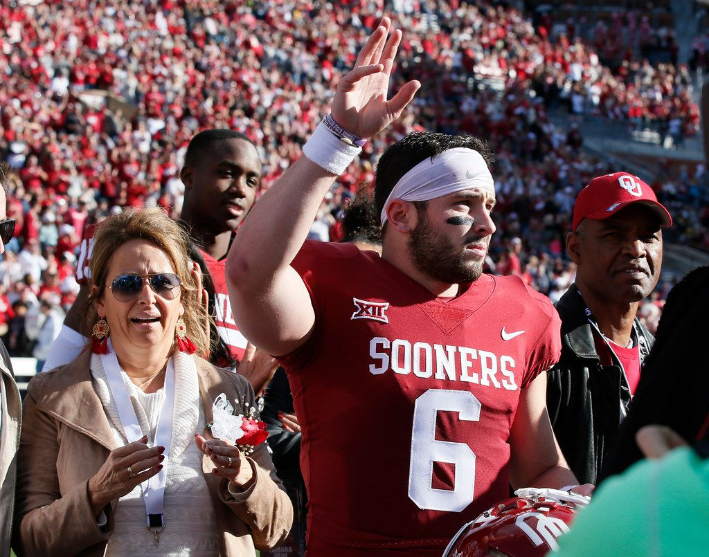 Oklahoma quarterback Baker Mayfield (6) waves to the crowd as he is announced on Senior Day, before the West Virginia-Oklahoma NCAA college football game in Norman, Okla., Saturday, Nov. 25, 2017. At left is his mom, Gina Mayfield. (AP Photo/Sue Ogrocki)