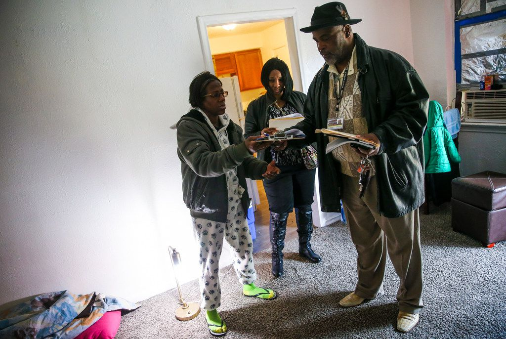 Dionne Lee, left, a tenant at Bryan Song Apartments who received a notice to vacate from the new management company, speaks with workers, who requested to not be named, from the Fair Housing Department.