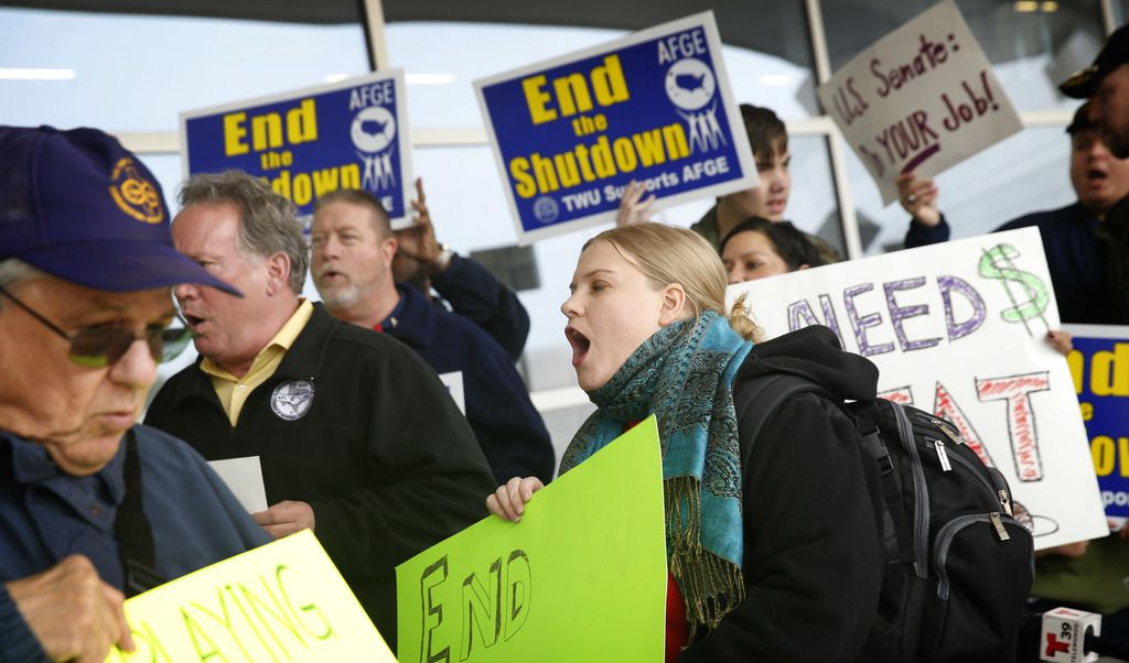 EPA worker and AFGE Local 1003 member Sarah Frey leads union and federal airport employees in a protest of the government shutdown outside Terminal D at Dallas-Fort Worth International Airport on Wednesday. Joining her are Texas State Employees Union retiree Kenneth Stretcher (left) and AFL-CIO Central Labor Council COO Mark York (second from left).