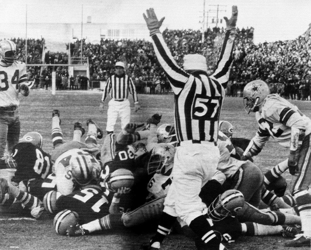 In this Dec. 31, 1967, photo, Green Bay Packers quarterback Bart Starr (15) digs his face across the goal line to score the winning touchdown against the Dallas Cowboys to bring the Packers their third consecutive NFL championship, in Green Bay, Wis.