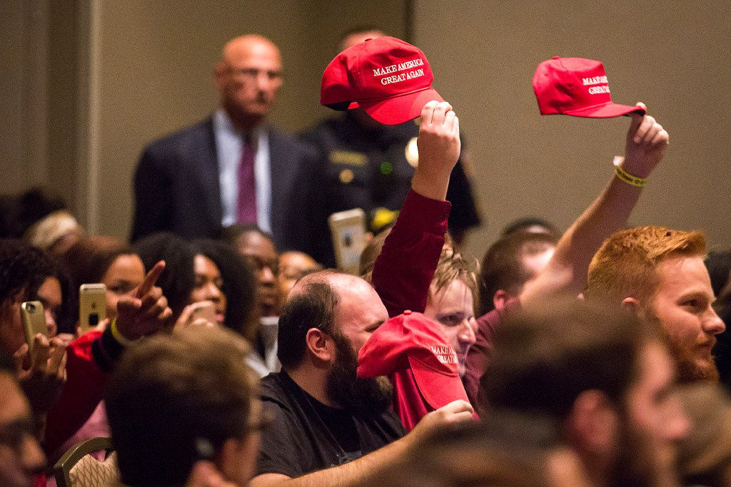 """Supporters hold up Donald Trump """"Make America Great Again"""" hats as Richard Spencer speaks at the Memorial Student Center at Texas A&M University on Tuesday, Dec. 6, 2016, in College Station, Texas. Spencer, a Dallas native and a self-professed founder of the """"alt right"""" movement, will speak at the campus at the invitation of a white nationalist and former student.  The university hosted the Aggies United event at Kyle Field, the university's football stadium, to overlap with Spencer's speech."""
