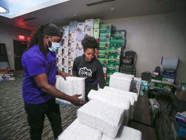 Volunteer Dominique Robinson, left, helps Christina Scott, Community Outreach Manager for Not My Son Dallas, sort donated diapers at a La Quinta hotel in North Dallas, Wednesday, February 24, 2021. Scott said that they need bath towels, black hair care products and baby wipes. Those wanting to donate can drop off items are the LaQuinta hotel at 13175 N Central Expressway. Not My Son, a civic engagement nonprofit, has been providing aid to people displaced by the winter storm since last week. They've spent thousands of dollars on hotel reservations while other organizations and local restaurants have donated food, hygiene products and other necessities. (Brandon Wade/Special Contributor)