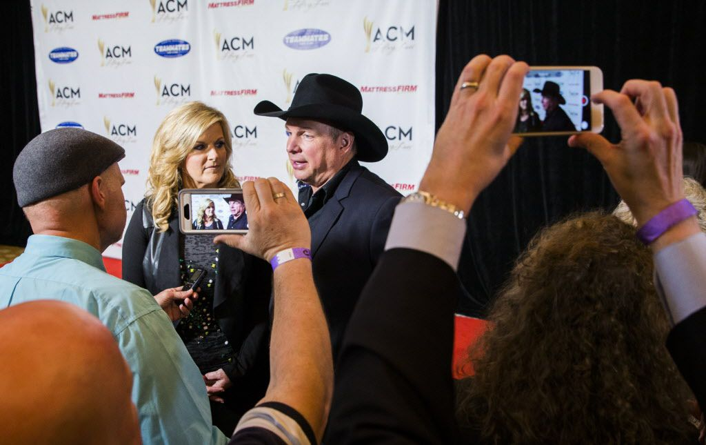 Country music stars Trisha Yearwood and Garth Brooks answer media questions on the red carpet.