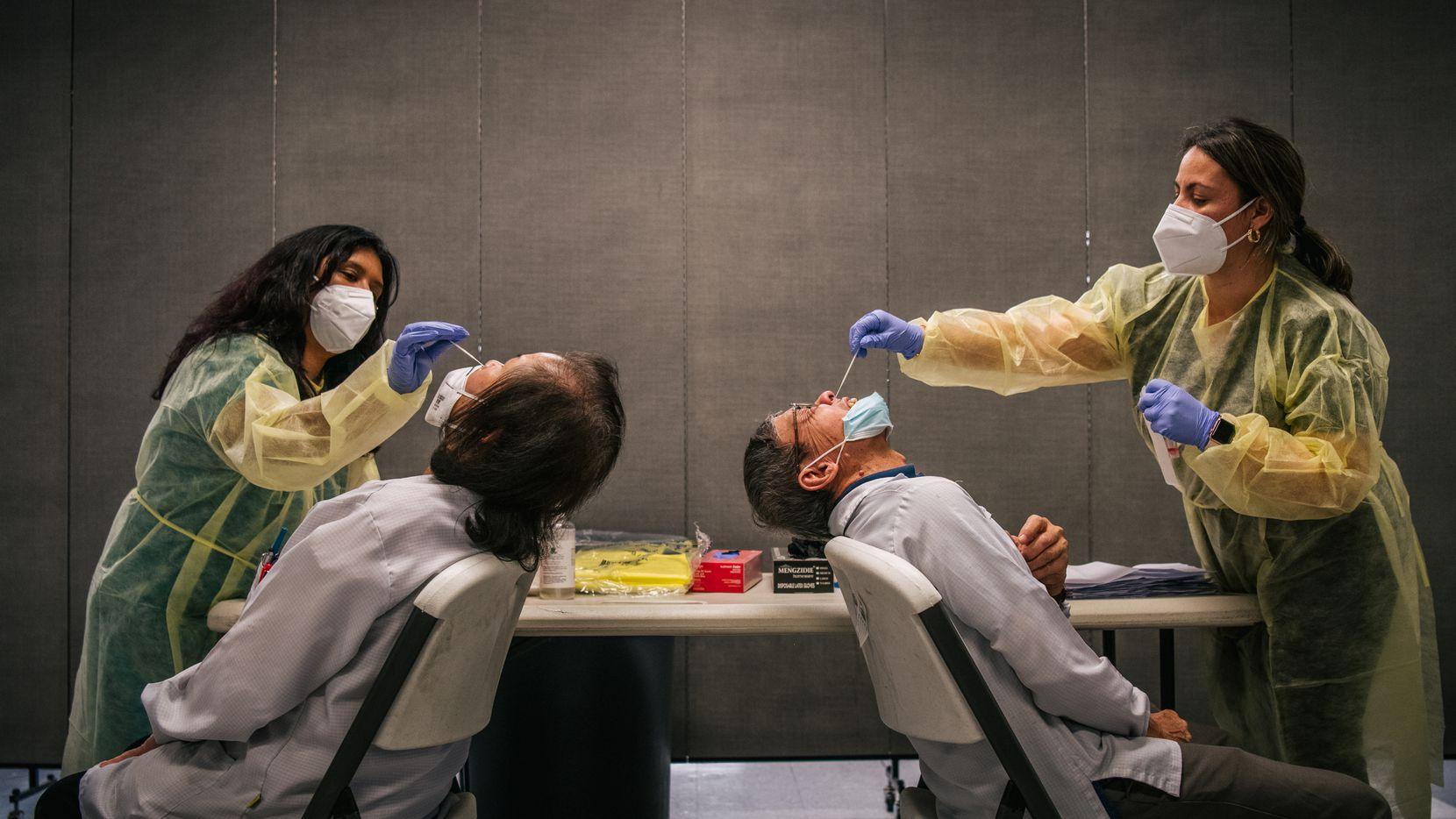 Las asistentes médicos Crystal Leyva (izquierda), y Keitia Perez realizan muestreos para hacer prueba de covid-19 el 13 de agosto de 2021, en Houston, Texas.