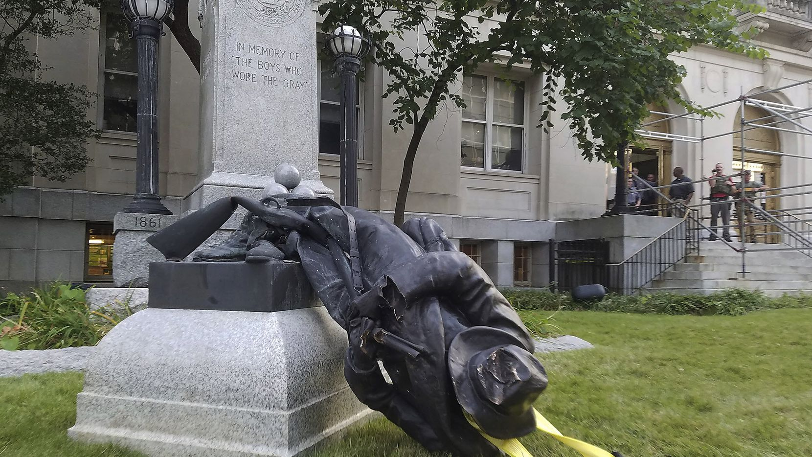 A toppled Confederate statue lies on the ground on Monday, Aug. 14, 2017, in Durham, N.C. Activists on Monday evening used a rope to pull down the monument outside a Durham courthouse. The Durham protest was in response to a white nationalist rally held in Charlottesville, Va, over the weekend.
