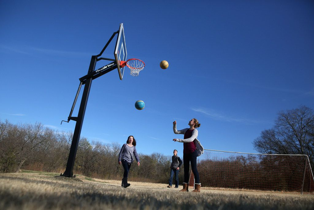 Kelly Blake (far right) played basketball with her sister Keaton Blake and brother Landon Blake at their home in McKinney.  An early study to build a bypass north of U.S. Highway 380 showed a freeway possibly cutting through their property.