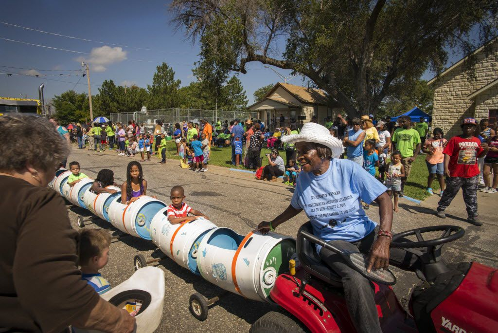 Bertha Carter pulls children in a makeshift train with her mower during a parade in Nicodemus, Kan., July 29, 2015. This town settled by freed slaves has dwindled to no more than 25 permanent residents, but the population swells during a weeklong homecoming for hundreds of descendants whose affection for the place runs deep.