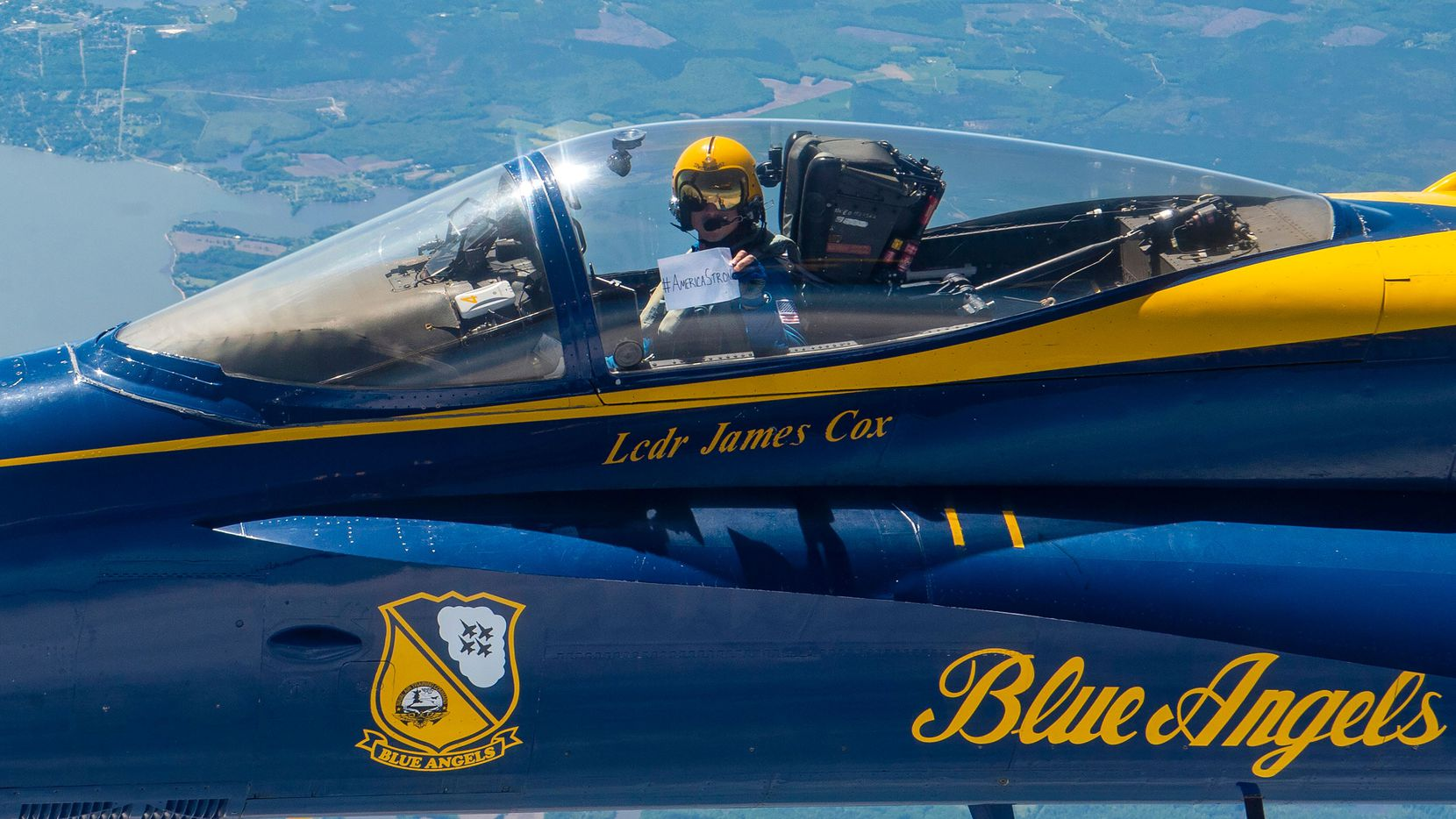 "Lt. Cmdr. Jim Cox, the U.S. Navy Flight Demonstration Squadron, the Blue Angels, slot pilot, displays an ""American Strong"" sign while transiting to Baltimore as part of Operation American Strong on May 2, 2020. - ""America Strong,"" to be held in various US cities, recognizes healthcare workers, first responders, military, and other essential personnel on the front lines fighting the COVID-19 pandemic, according to the US Defense Department. (Photo by Christopher GORDON / US NAVY / AFP)"