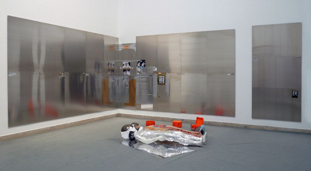 The Nasher Sculpture Center announces German artist Isa Genzken as the recipient of the 2019 Nasher Prize, which honors a living artist who elevates the understanding of sculpture and its possibilities. Shown is OIL XV / OIL XVI,  2007,  installation wall piece; 23 panels in three segments: aluminium, metal foil, adhesive tape, metal, printed paper  265 x 450 cm; 265 x 450 cm; 270 x 132 cm floor piece, six parts: two mannequins, two plastic cases, one glass bowl, metal foil, plastic, fabric, 35 x 220 x 380 cm.