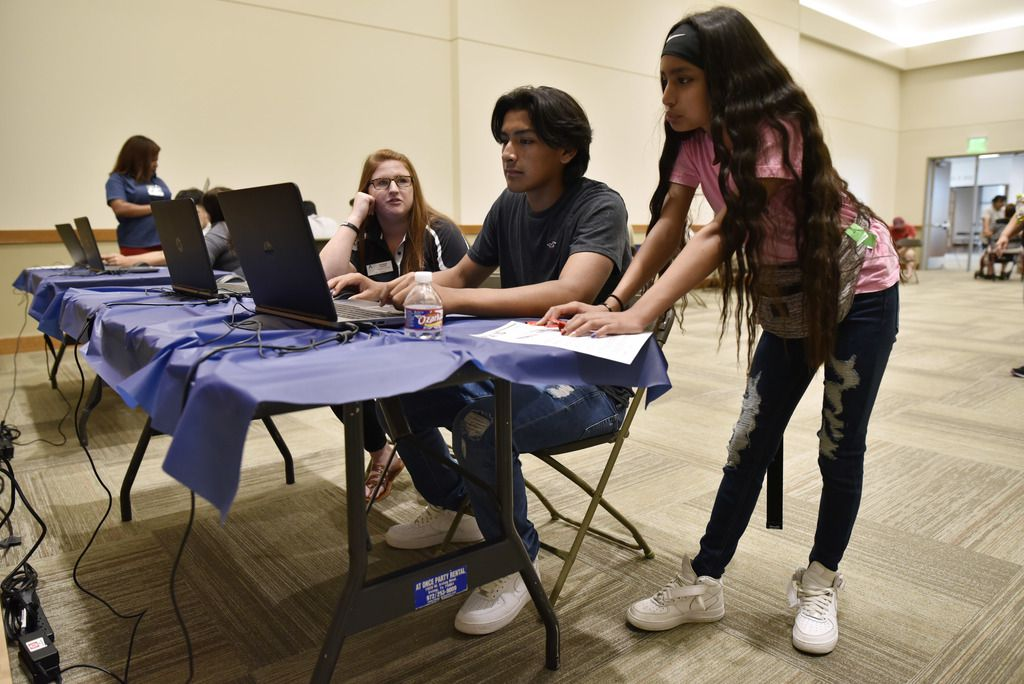 Shannon Shaver, an admissions counselor, helps Sebastián Ovalle,16, and his sister Isabela, during a Dallas College event.
