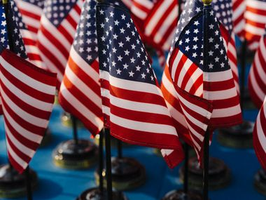 American flags at a naturalization ceremony on July 4th. Immigrants fear the Trump administration is becoming more aggressive in enforcing laws against newcomers, even those here legally.