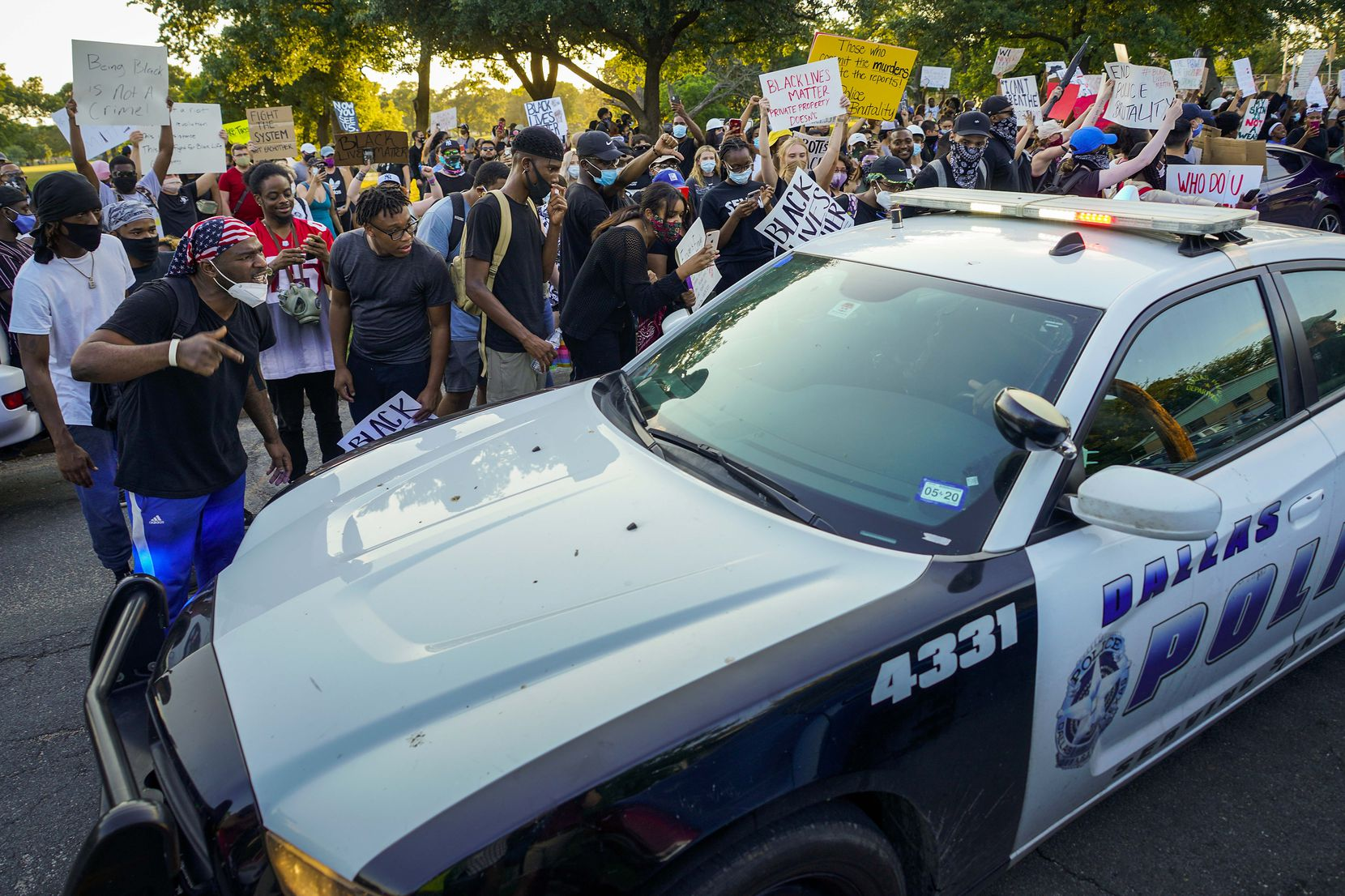 A group of demonstrators yells at a passing Dallas police vehicle at Lake Cliff Park as protests continue after the death of George Floyd on Tuesday, June 2, 2020, in Dallas. Because of the city imposed 7:00 p.m. curfew, the group moved from Dallas City Hall to outside the curfew zone in Oak Cliff.