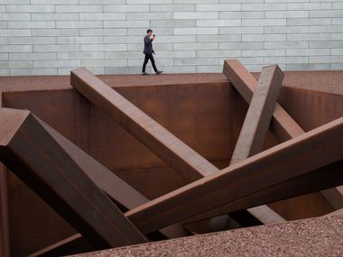 "A man tours artist Michael Heizer's ""Collapse,"" a sculpture of 15 steel beams arranged in a 16-foot hole, as he tours the Pavilions, a new building at the Glenstone Museum, combining art, architecture and landscape."
