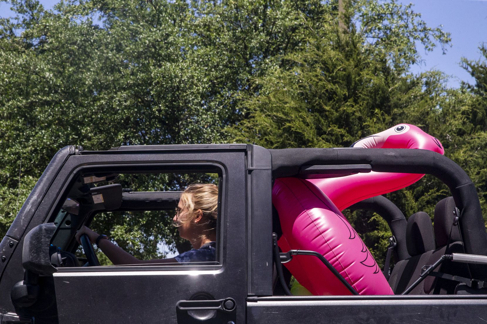 Karina Boyea (center) and her sister Marley (not pictured, passenger seat) drive to a pool party held by a small group of friends in Dallas on Friday, May 1, 2020. Marley Boyea said they're not generally happy about the state reopening businesses, and have no plans to visit malls or theaters any time soon — instead, they're opting to spend time outside.