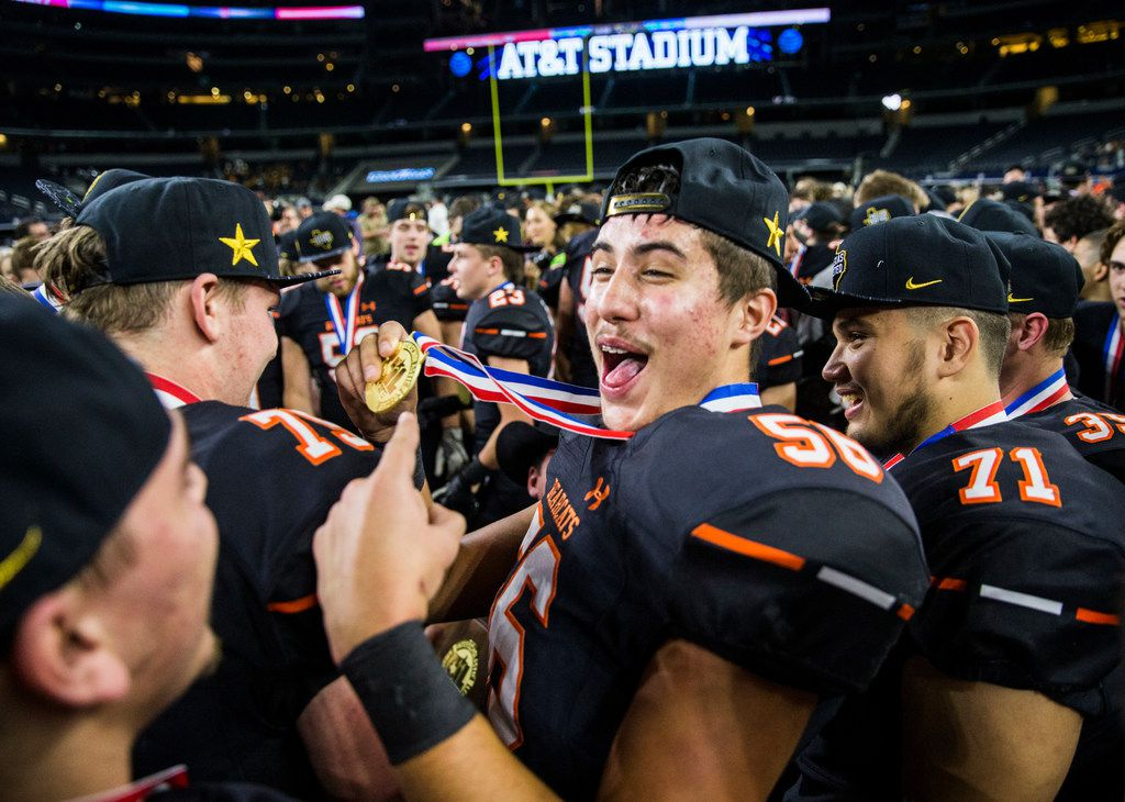 Aledo offensive lineman Cayden Glasgow (56) holds up his gold medal as he and his team celebrate a 55-19 win over Fort Bend Marshall, making them the UIL Class 5A Division II football state champions on Friday, December 21, 2018 at AT&T Stadium in Arlington.
