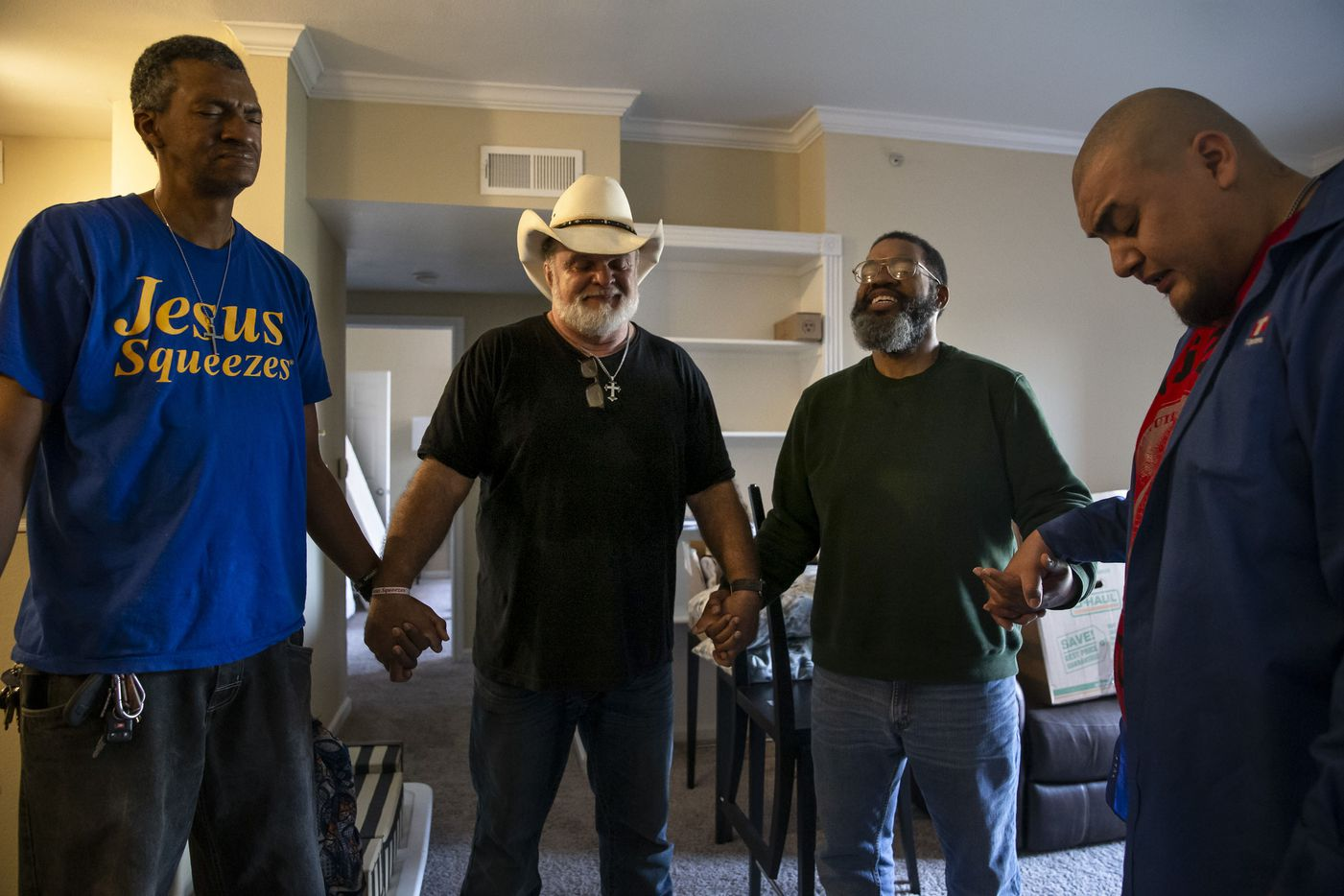 """From left: S.O.U.L. Church members Gerry """"Slim"""" Debnam, Pastor Leon Birdd, Randy Thornton and Israel Alonzo prayed to bless Thornton's new Cityplace apartment after helping him move in with donated furniture and other belongings on  Jan. 14, 2020. Thornton said he'd found a spiritual family at S.O.U.L. Church. """"Blood is thicker than water, but the Spirit will override everything,"""" he said."""