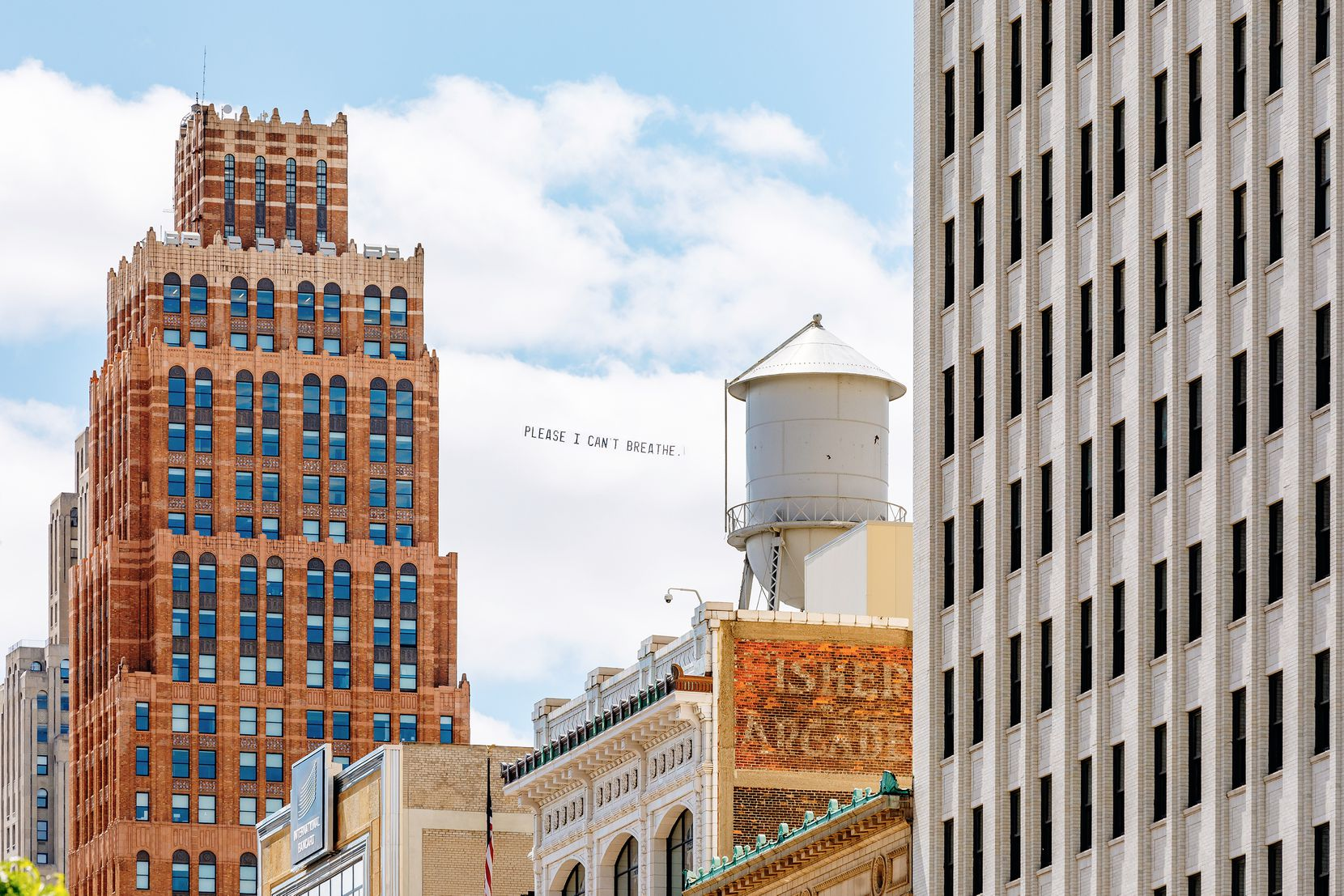 """A banner reading """"Please I can't breathe,"""" which were among George Floyd's last words, trails behind a plane flying over Detroit as part of an artwork by Dallas artist Jammie Holmes."""
