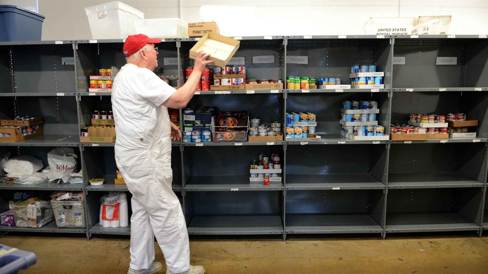 John Carpenter, a volunteer at the Irving Cares food pantry, restocks shelves in this 2013 file photo.