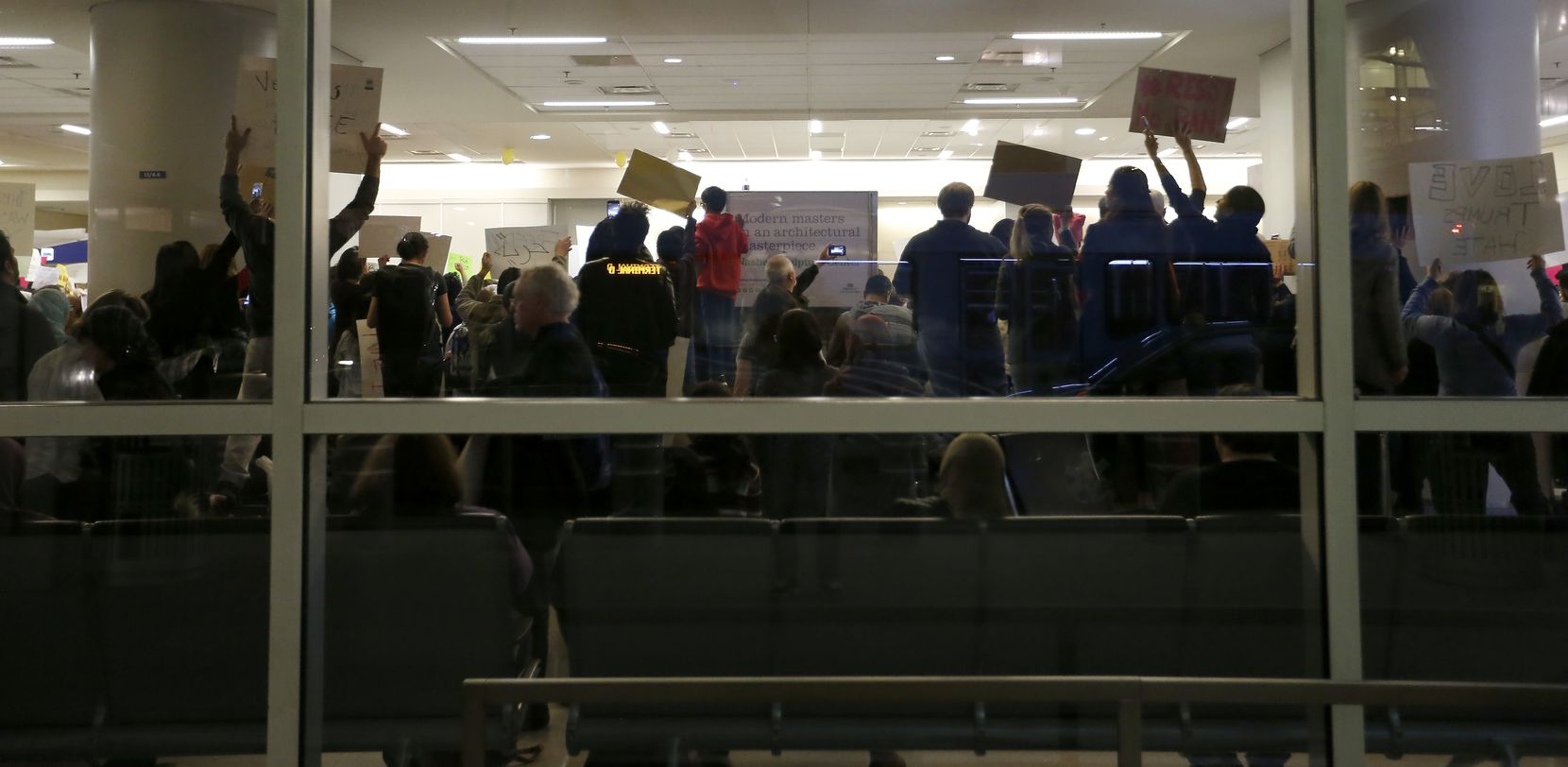 Protesters hold signs against Trump's executive order banning people coming from certain countries inside the Terminal D at Dallas/Fort Worth International Airport in Dallas, Saturday, Jan. 28, 2017.