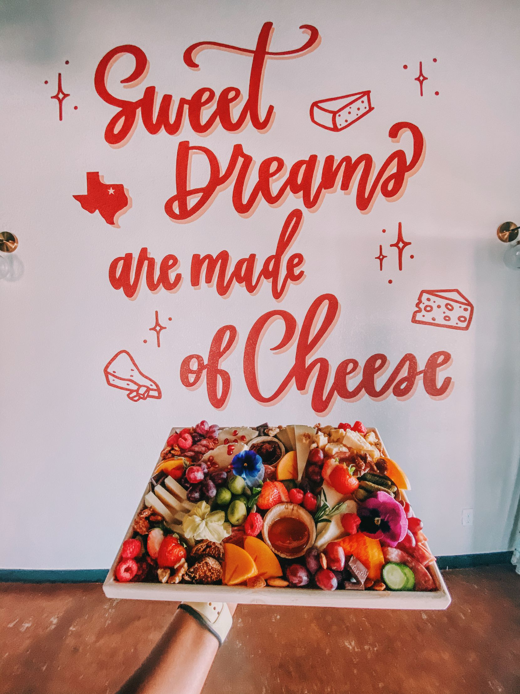"""YaYaYum Boards' storefront in downtown Grapevine, which is only accepting takeout orders right now, features a mural with the words """"Sweet dreams are made of cheese."""""""