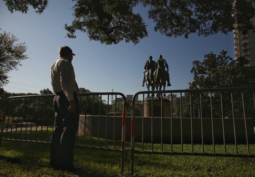 A passer-by viewed the statue of Confederate Gen. Robert E. Lee at Lee Park on Thursday. (Andy Jacobsohn/Staff Photographer)