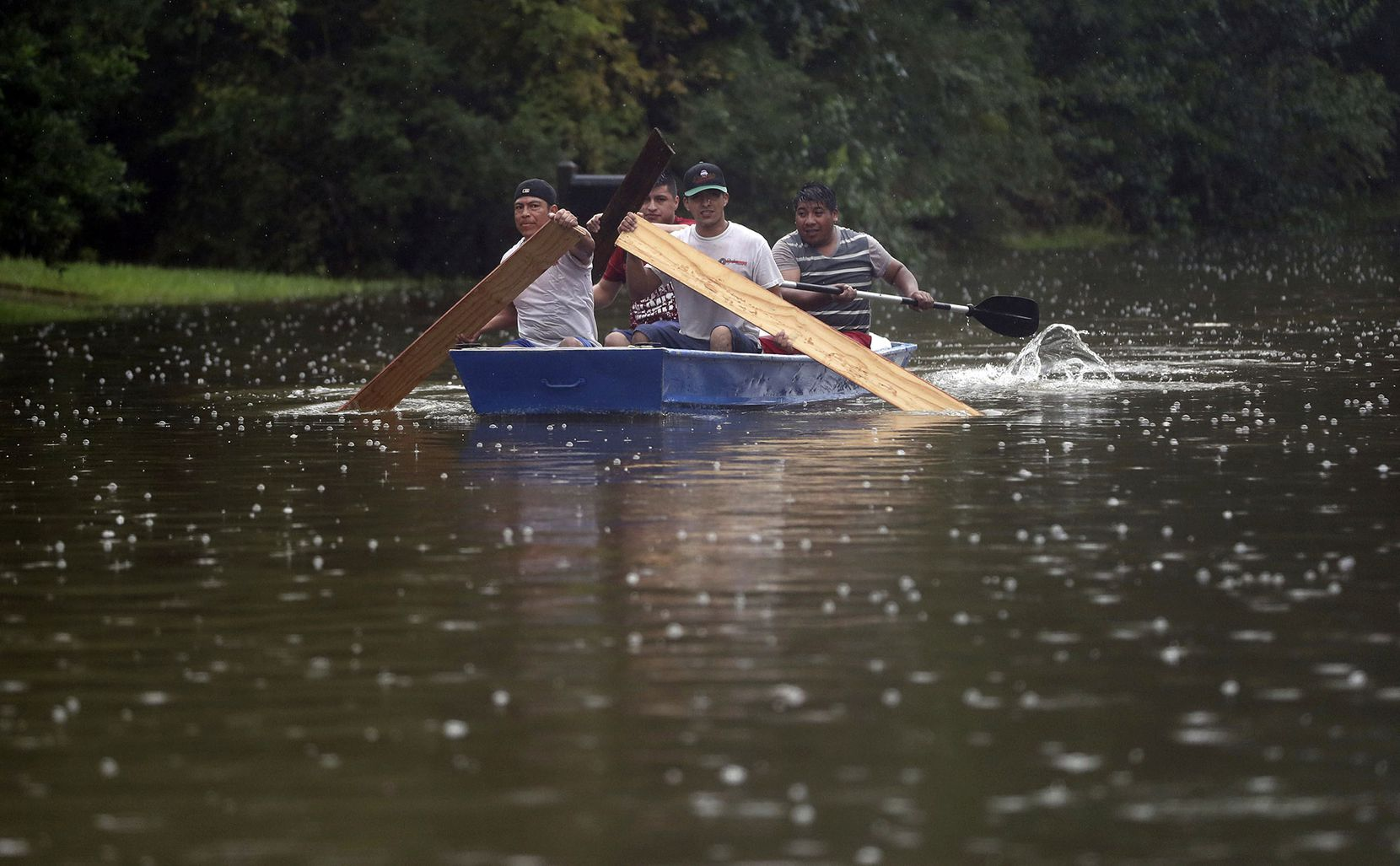 People use plywood to row a boat down Deats Road in Dickinson, Texas, Monday, Aug. 28, 2017, as floodwaters from Tropical Storm Harvey rise. (Kelsey Walling/The Galveston County Daily News via AP)