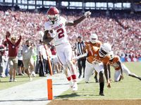 Oklahoma Sooners wide receiver CeeDee Lamb (2) scores a touchdown after passing Texas Longhorns defensive back D'Shawn Jamison (5) during the second half of play in the Red River Showdown at the Cotton Bowl in Dallas on Saturday, October 12, 2019. Oklahoma Sooners defeated Texas Longhorns 34-27.