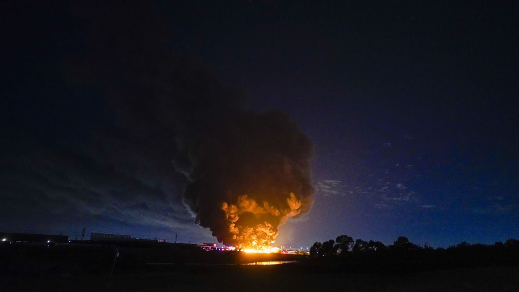A plume of smoke is seen from a massive fire at  Poly-America on Wednesday, Aug. 19, 2020, in Grand Prairie.