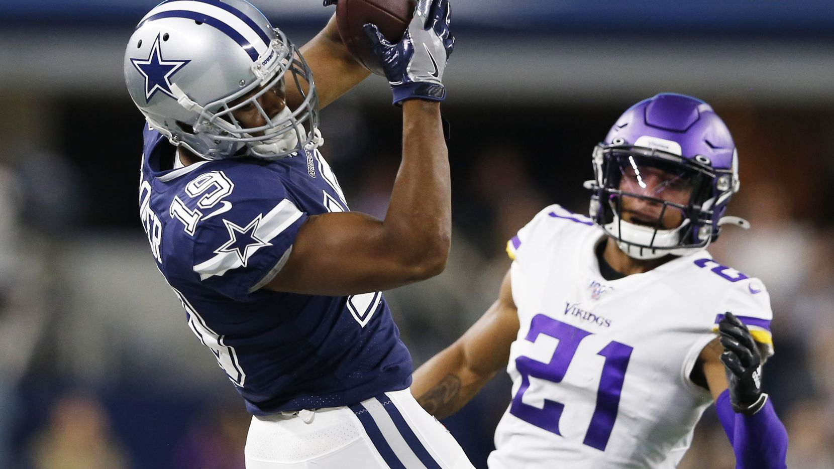 FILE - Cowboys wide receiver Amari Cooper (19) catches a pass in front of Vikings cornerback Mike Hughes (21) during the first half of play at AT&T Stadium in Arlington on Sunday, Nov. 10, 2019.