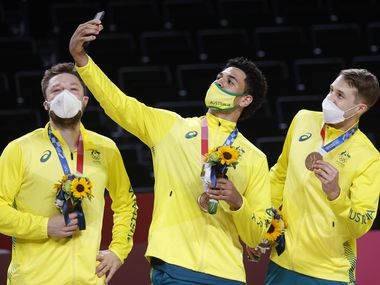 Australia's Matthew Dellavedova (8, left) looks on as Josh Green (6, center) and Nathan Tobey (9, right) take a photo together during the medal ceremony at the postponed 2020 Tokyo Olympics at Saitama Super Arena, on Saturday, August 7, 2021, in Saitama, Japan. Australia defeated Slovenia 107–93.  (Vernon Bryant/The Dallas Morning News)