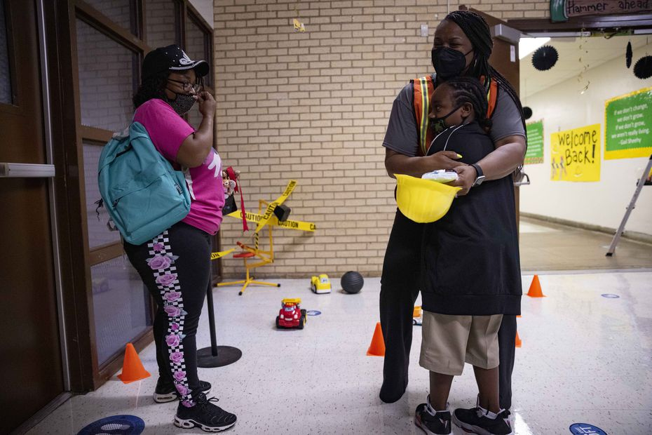 Mom Chequetta Shed (left) watches as Principal Shanieka Christmas-McDonald hugs her son Donald Burney Jr., 9, during the first day of school on Monday, Aug. 2, 2021, at H.I. Holland Elementary School in Dallas. (Juan Figueroa/The Dallas Morning News)